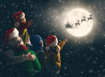 Family enjoying Christmas. Merry Christmas and happy holidays! Cute little children with mom, dad, grandma and grandpa. Santa Claus flying in his sleigh against stock photography
