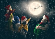 Family enjoying Christmas. Merry Christmas and happy holidays! Cute little children with mom, dad, grandma and grandpa. Santa Claus flying in his sleigh against royalty free stock image