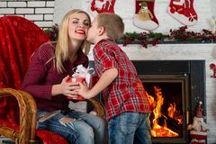Merry Christmas and Happy Holidays!Cute son gives his beloved mother a gift.New year`s interior in the living room with fireplace. Cute son gives his beloved Stock Photo