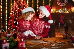 Merry Christmas and Happy Holidays. Cheerful cute curly little girl and her older sister in santas hats cooking stock photos