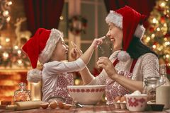 Cooking Christmas cookies. Merry Christmas and Happy Holidays. Family preparation holiday food. Mother and daughter cooking cookies royalty free stock image