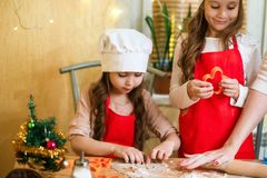 Merry Christmas and Happy Holidays. Family preparation holiday food. Mother and daughters cooking Christmas cookies. stock photo
