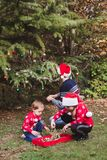 Merry Christmas and Happy Holidays. Father in red Christmas hat and two daughters in red sweaters decorating the Christmas tree ou royalty free stock image