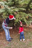 Merry Christmas and Happy Holidays. Father in red Christmas hat and daughter in red sweater decorating the Christmas tree outdoor stock image