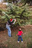 Merry Christmas and Happy Holidays. Father in red Christmas hat and daughter in red sweater decorating the Christmas tree outdoor royalty free stock image