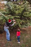 Merry Christmas and Happy Holidays. Father in red Christmas hat and daughter in red sweater decorating the Christmas tree outdoor stock photo