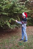 Merry Christmas and Happy Holidays. Father in red christmas hat decorating the Christmas tree outdoor in the yard of the house bef. Ore holidays in europe stock photos