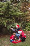 Merry Christmas and Happy Holidays. Father in red Christmas hat and two daughters in red sweaters decorating the Christmas tree ou stock photography