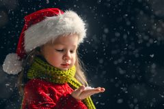 d2c6a76457cce Girl on snowy background. Merry Christmas and happy holidays! Little girl  blowing on snow