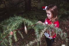 Merry Christmas and Happy Holidays. little girl decorating the Christmas tree outdoor in the yard of the house before holidays royalty free stock photo