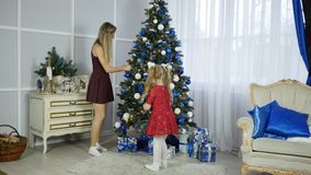 Mom and daughter decorate Christmas tree stock video footage