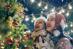 Mom and daughter decorate Christmas tree Royalty Free Stock Photography