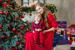 Merry Christmas and Happy Holidays Mom and daughter decorate the tree in room. Loving family indoors royalty free stock image