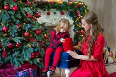 Merry Christmas and Happy Holidays Mom and daughter decorate the tree in room. Loving family indoors royalty free stock photos