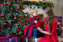 Merry Christmas and Happy Holidays Mom and daughter decorate the tree in room. Loving family indoors stock photos