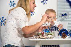 Merry Christmas and happy holidays!Mother and son painting a snowflake.Family creates decorations for Christmas interior. Mother and son painting a snowflake stock image