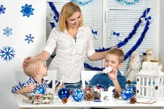 Merry Christmas and happy holidays!Mother and two sons painting a snowflake.Family creates decorations for Christmas interior. Mother and two sons painting a royalty free stock photo