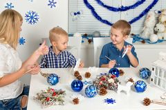 Merry Christmas and happy holidays!Mother and two sons painting a snowflake.Family creates decorations for Christmas interior. Merry Christmas stock photography