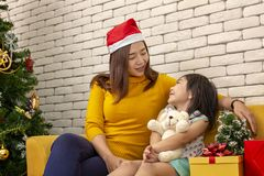 Merry Christmas and Happy Holidays or Happy New Year Mother gave a gift to a cute girl. The girl hugs the teddy bear that the royalty free stock images