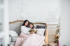 Merry Christmas and Happy Holidays. Pretty young mom reading a book to her cute daughter near Christmas tree indoors.  Stock Images