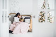 Merry Christmas and Happy Holidays. Pretty young mom reading a book to her cute daughter near Christmas tree indoors.  Royalty Free Stock Image