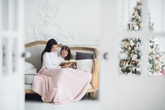 Merry Christmas and Happy Holidays. Pretty young mom reading a book to her cute daughter near Christmas tree indoors.  Stock Image