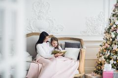 Merry Christmas and Happy Holidays. Pretty young mom reading a book to her cute daughter near Christmas tree indoors Stock Image