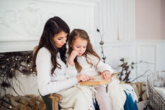 Merry Christmas and Happy Holidays, Pretty young mom reading a book to her cute daughter near tree indoors. Stock Photos