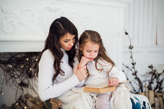 Merry Christmas and Happy Holidays, Pretty young mom reading a book to her cute daughter near tree indoors. Stock Photography