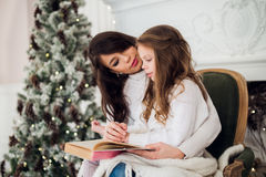 Merry Christmas and Happy Holidays, Pretty young mom reading a book to her cute daughter near tree indoors. Merry Christmas and Happy Holidays, Pretty young mom Royalty Free Stock Photography