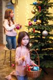 Merry Christmas and Happy Holidays. Two cute little girls are decorating the Christmas tree at home room. stock image