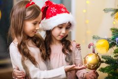 Merry Christmas and Happy Holidays. Two cute little girls are decorating the Christmas tree at home room. stock photos