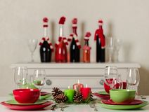 Merry Christmas and Happy New Year! Тable setting festive decor - green and red dishes, candles and fir cones. Knitted decor - royalty free stock photography