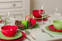 Merry Christmas and Happy New Year! Тable setting festive decor - green and red dishes, candles and fir cones. Knitted decor - royalty free stock image