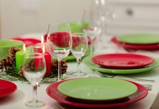 Merry Christmas and Happy New Year! Тable setting festive decor - green and red dishes, candles and fir cones. Knitted decor - stock photography