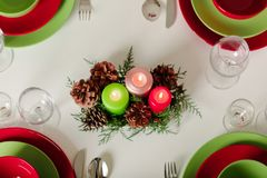 Merry Christmas and Happy New Year! Тable setting festive decor - green and red dishes, candles and fir cones. Knitted decor - stock images