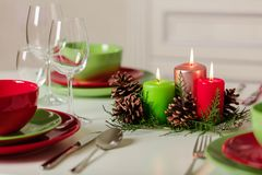 Merry Christmas and Happy New Year! Тable setting festive decor - green and red dishes, candles and fir cones. Knitted decor - royalty free stock images