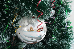 Merry Christmas and Happy New Year!. White glass sphere on a New Year's tree Stock Photo