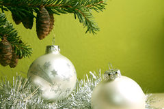 Merry christmas and a happy new year. Silver colored christmas balls in front of a green background royalty free stock image