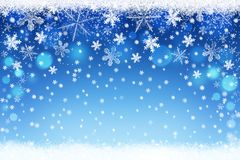 Merry Christmas and Happy New Year background. Beautiful abstract white and silver snowflakes on blue bokeh winter snow landscape backdrop Stock Images