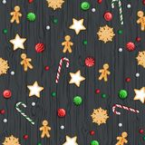 Merry Christmas and Happy New Year Background. Winter traditional sweets, biscuit, cookie, lollipops, candies, candy cane. Gingerbread Man on a wooden black Stock Photography