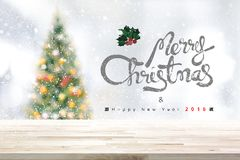 Merry Christmas and happy new year 2018 background with wood tab. Le top, blurred decorated pine tree and white snow falling  - can be used for display or Royalty Free Stock Photos