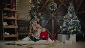 Merry Christmas and Happy New Year. Beautiful family in Xmas interior. Pretty young mother reading a book to her. Merry Christmas and Happy New Year. Beautiful stock video