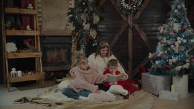 Merry Christmas and Happy New Year. Beautiful family in Xmas interior. Pretty young mother reading a book to her. Merry Christmas and Happy New Year. Beautiful stock video footage