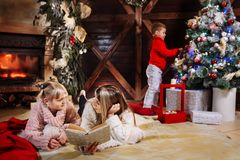 Merry Christmas and Happy New Year. Beautiful family in Xmas interior. Pretty young mother reading a book to her royalty free stock images