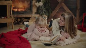 Merry Christmas and Happy New Year. Beautiful family in Xmas interior. Pretty young mother reading a book to her. Merry Christmas and Happy New Year. Beautiful stock footage