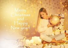 Merry Christmas and Happy New Year! beautiful young woman with long hair in knitted sweater sitting indoor decorated lights. Candles gifts balls stars. Magic stock image