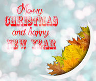 Merry Christmas And Happy New Year on blue bokeh background with leaves Stock Photography