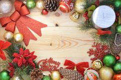 Merry christmas and happy new year. Candle and Merry christmas sign on wooden board with christmas tree ornaments and green and red decoartions: bows, ribons stock photo