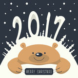 Merry Christmas and Happy New Year. Christmas card. Brown bear lies on a snowdrift . On the mountain a bear figures 2,0,1,7. It`s snowing. Brown bear holds a Stock Photos